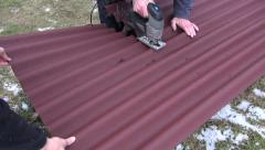 worker cuts with electric saw, corrugated sheet roof - stock footage