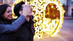 Young woman surprises his boyfriend by blindfolding his eyes in city HD Stock Footage