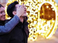 Young woman surprises his boyfriend by blindfolding his eyes in city during NTSC Stock Footage