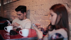 Young couple using and staring at smartphone while sitting in cafe HD - stock footage