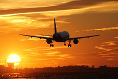airplane landing at an airport during sunset - stock photo