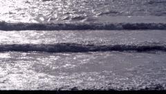 Small waves lapping sun glistening Stock Footage