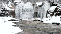 Winter view over foamy stream into cascade of waterfal. Stream in deep freeze. - stock footage