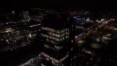 Aerial - Skyscraper with bright illumination office interior at night Stock Footage