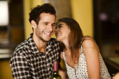 Young woman whispering into her boyfriend's ear Stock Photos
