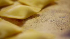 Laying raw ravioli pasta on a tray with flour. Stock Footage