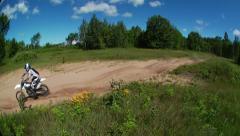 Dirt biker goes by on rough terrain Stock Footage