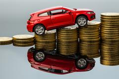 rising car costs. car on coins - stock photo
