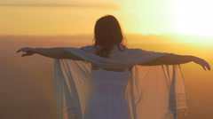 Relaxing beautiful woman  contemplates the sunset on top of a mountain Stock Footage