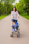Happy mom pushing pram with toddler in park - stock photo