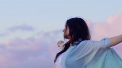 Relaxing young woman opens arms to the sky suggestive clouds in background Stock Footage