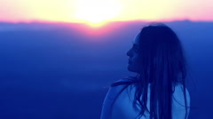 Thoughtful woman is relaxing at the sunset: dusk, meditation, relaxation, peacef Stock Footage