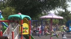Great playground outdoors, lot of children having fun, swings toys and carrousel Stock Footage