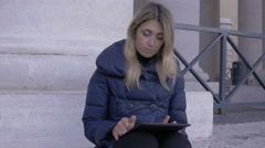 Young woman using tablet pc sitting on the stairs of St. Peter square in Rome Stock Footage