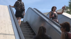 Commuters going in and out of subway station in midday escalators use, no effort Stock Footage