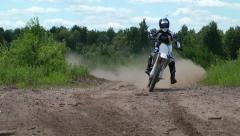 Motocross dirtbike drives fast on dirt road Stock Footage