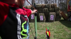 Boy Shooting Bow and Arrow Hay-bail target from over the shoulder - stock footage