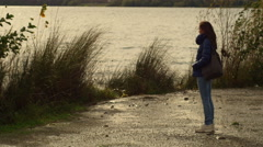 Young woman standing alone and sad near a lake in a cold winter day: thoughtful Stock Footage