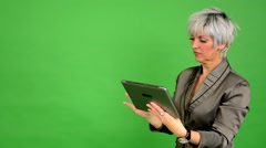 Business middle aged woman works on tablet - green screen - studio Stock Footage