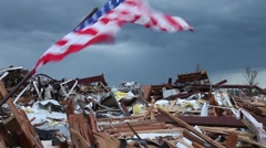 American flag in a pile of debris from tornado destruction blown by wind - stock footage