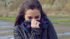 Young woman covering her face with a scarf on a cold winter day Stock Footage