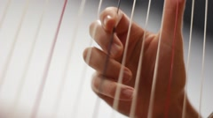 Close-up clip of a female harpist's hands playing a harp Stock Footage