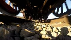 Rail track POV - Undercarriage of moving locomotive, slow motion Stock Footage