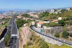 aerial view of funchal and highway, build against the mountains of madeira is - stock photo