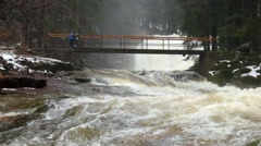 Person on bridge above troubled water. Huge stream of rushing water masses - stock footage