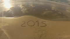 Year 2015 written on sand at sunset, aerial view Stock Footage