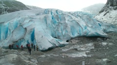 Tourists approach a glacier mouth in Norway Stock Footage