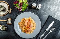 Farfalle with tomato sauce and roasted salmon Stock Photos