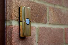 Brass-coloured doorbell on a brick wall - stock photo