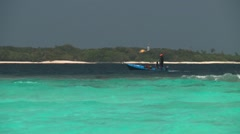 Fishermen on a boat pass a disappearing low-lying island in the Maldives Stock Footage