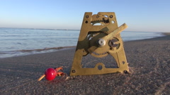 Antique brass clock gears and rose hip on  sea beach sand. Time  concept Stock Footage