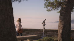 Girl on a terrace looks at the panorama and throuh a spyglass - wide shot Stock Footage