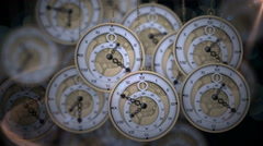 Hanging pocket watches ticking in shadows Stock Footage
