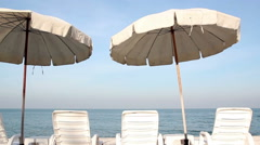 White sunbeds and umbrella on the beach in Thailand Stock Footage