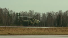 Military helicopter lands on airstrip - stock footage