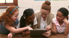 Smiling teacher and pupils using tablet pc in classroom - stock footage