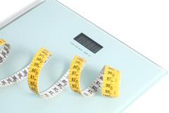 Close up of a scale with a tape measure - stock photo