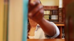Pretty teacher taking book from shelf Stock Footage