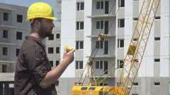 Young male enginner at construction site, having lunch eating fresh golden apple Stock Footage