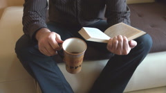 Headless view of businessman at home, read favorite book, drinking cup of coffee - stock footage