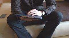 Man sitting on living room couch open clipboard with working papers, reading Stock Footage