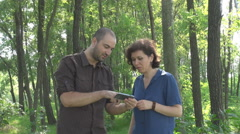Young man and woman in the forest checking geographical coordinates, lost people - stock footage