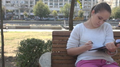 Female student in park learning for exams, writing and taking notes, stressful Stock Footage