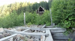 Stock Video Footage of ruins of a wooden dam and beautiful trees and conifers green bushes