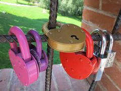 Love padlocks affixed to a bridge fence in park - stock photo