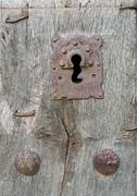 Stock Photo of Old run-down wooden door and iron lock